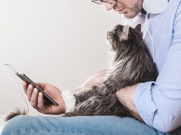 Śliczny, Puszysty Kotek I Mężczyzna Z Telefonem. Koncepcja Opieki Nad Zwierzętami Premium Zdjęcia