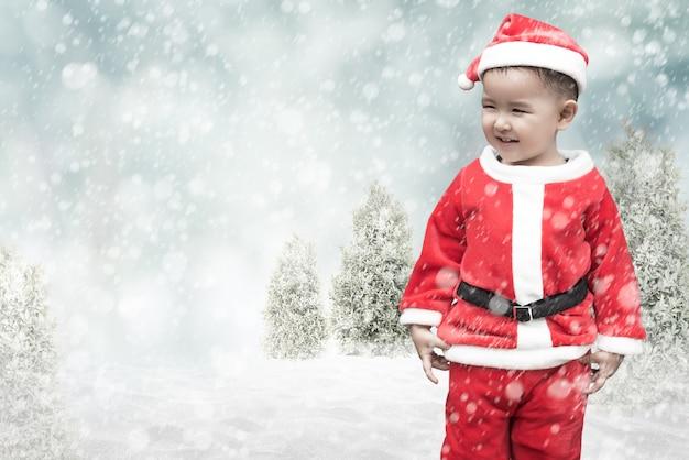 Śliczny santa dzieciak z spada śniegiem Premium Zdjęcia