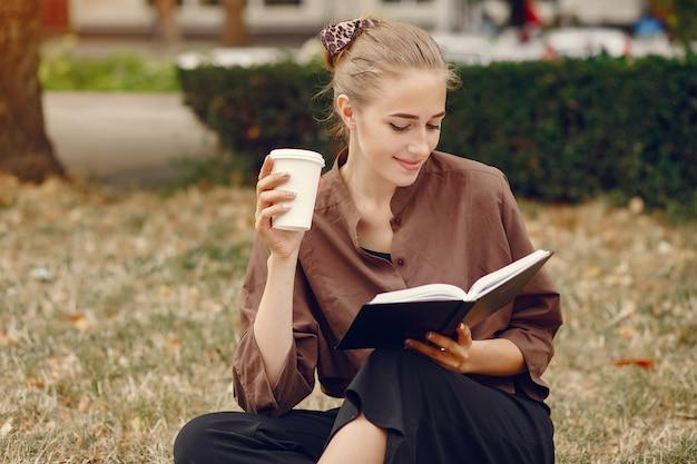 Śliczny uczeń pracuje w parku i używa notatnika Darmowe Zdjęcia