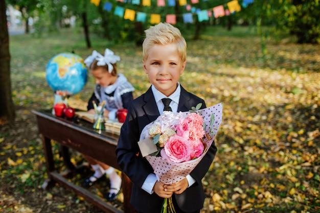 Śliczny Uczeń W Mundurku Szkolnym Trzyma Bukiet Premium Zdjęcia