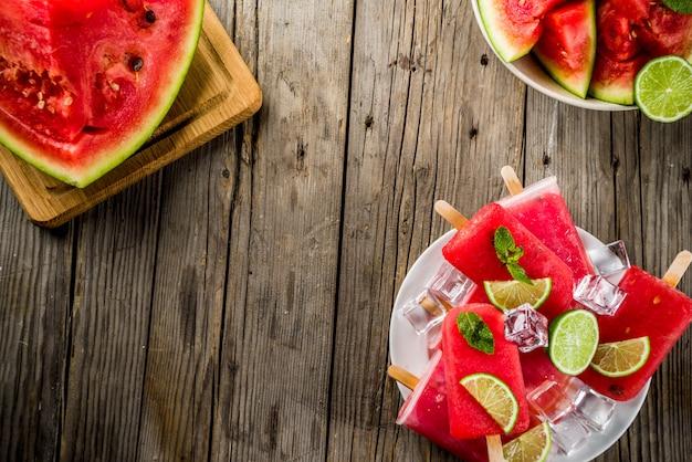Słodcy lato arbuza i wapna popsicles z pokrojonym arbuzem i mennicą, na bielu marmuru tła kopii przestrzeni Premium Zdjęcia