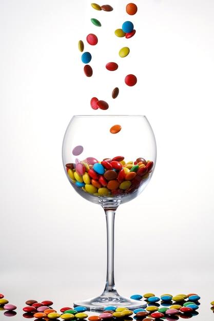 Słodka Kolorowa Cukierek Pokrywająca Czekolada Spada Wewnątrz Szkło Na Białym Tle. Premium Zdjęcia
