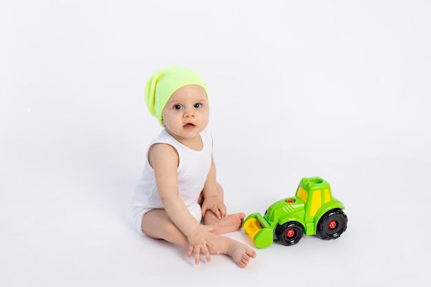 Słodki Chłopczyk W Białym Body Na Białej ścianie Izolowanej Bawiący Się Maszyną Do Pisania, Wczesny Rozwój Dzieci, Dziecko 8 Miesięcy Wśród Zabawek, Premium Zdjęcia
