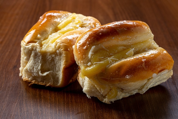 Słodki Krem Waniliowy Chleb Na Brązowym Drewnianym Stole. Jest To Rodzaj Chleba Powszechnego W Brazylii I Portugalii, Wyrabiany Ze Słodkiego Ciasta. Premium Zdjęcia