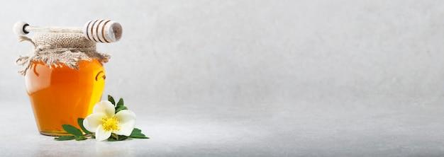 Słodki Miód W Szklanym Słoju. Jasnoszare Tło Premium Zdjęcia