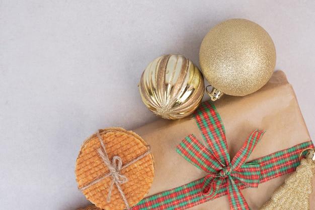 Słodkie Ciasteczka W Liny Z Prezentem I świąteczną Złotą Zabawką Na Białej Powierzchni Darmowe Zdjęcia
