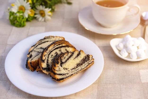 Słodkie ciasto makowe na talerzu, na stole i filiżankę herbaty Premium Zdjęcia