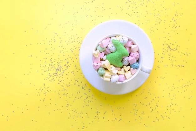 Słodkie Cukierki I Pianki W Filiżance Na żółtym Tle, Widok Z Góry. Koncepcja Wiosny, Wielkanocy, Stylu życia. Premium Zdjęcia
