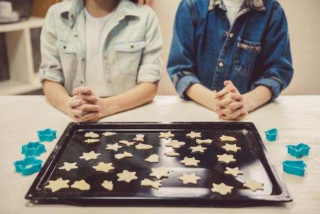 Słodkie dzieci układanie ciasteczek na blasze. Premium Zdjęcia