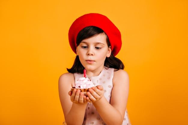Słodkie Dziecko Brunetka Robi życzenia Urodzinowe. Preteen Dziewczyna W Czerwonym Berecie Zdmuchuje świecę Na Torcie. Darmowe Zdjęcia