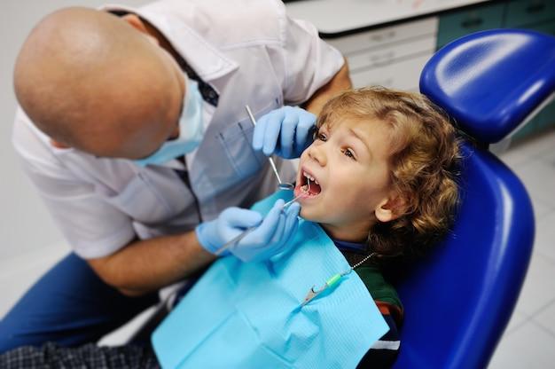 Słodkie dziecko w sweter w paski na recepcji u dentysty Premium Zdjęcia