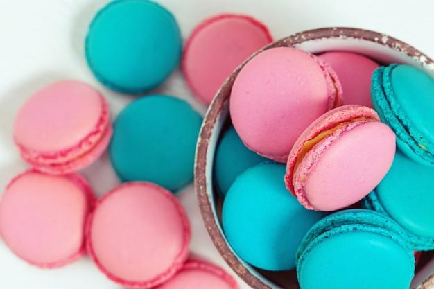 Słodkie kolorowe makaroniki z bliska w misce na drewnianym stole biały. t Premium Zdjęcia