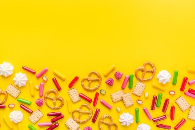 Słodycze płaskie leżały na żółtym tle Darmowe Zdjęcia