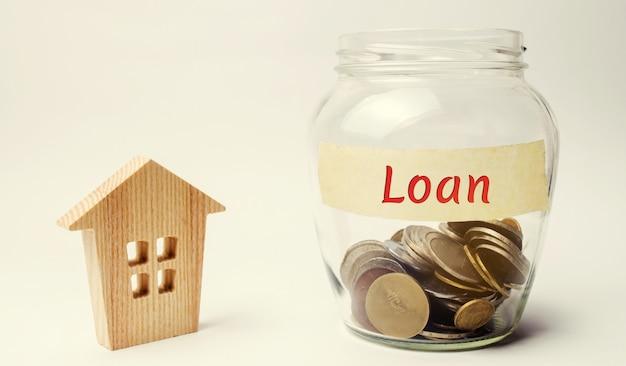 Słoik z napisem pożyczka i mały drewniany dom. kupno domu w długach. Premium Zdjęcia