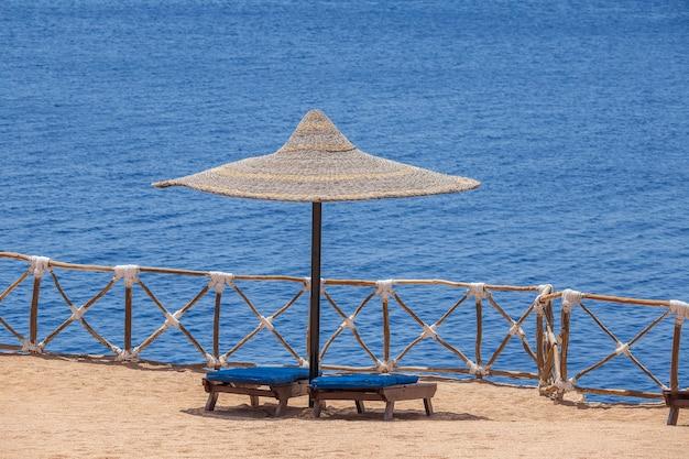 Słomiane Parasole Z Drewnianymi Leżakami Obok Wody Morskiej Na Piaszczystej Plaży W Egipcie Premium Zdjęcia