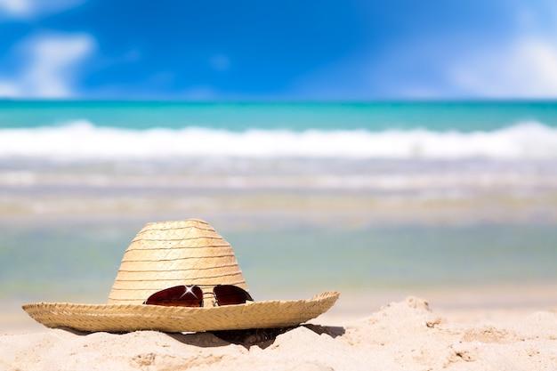 Słomiany Kapelusz Z Okularami Przeciwsłonecznymi Na Białym Piasku Przeciw Turkus Wody Zadziwiającemu Oceanowi I Niebieskiemu Niebu Premium Zdjęcia