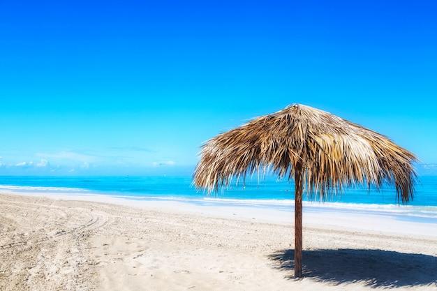 Słomiany Parasol Na Pustej Nadmorski Plaży W Varadero, Kuba. Premium Zdjęcia