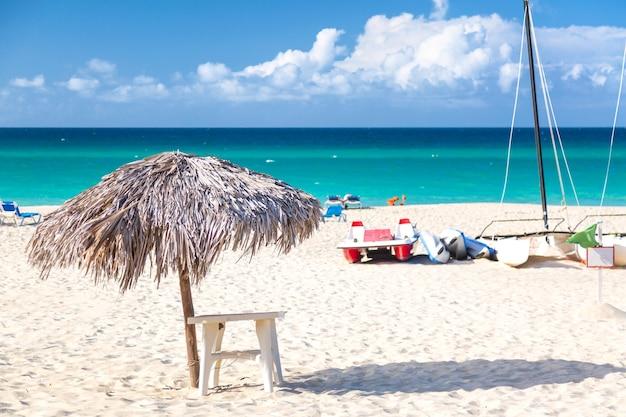 Słomiany Parasol Na Pustej Nadmorskiej Plaży Z żaglówką W Varadero Na Kubie. Premium Zdjęcia