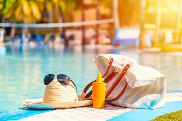 Słomkowy Kapelusz Z Okularami Przeciwsłonecznymi W Pobliżu Butelki Z Kremem Z Filtrem Przeciwsłonecznym I Torbą Plażową Na Powierzchni Niebieskiego Przezroczystego Basenu. Premium Zdjęcia