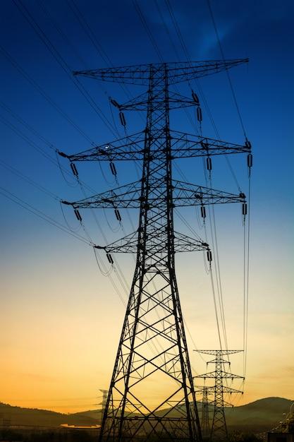 Słońce ustawione za sylwetką słupów elektrycznych Darmowe Zdjęcia