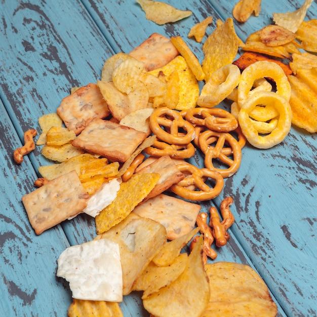 Słone przekąski. precle, frytki, krakersy na drewnianym. niezdrowe produkty Premium Zdjęcia