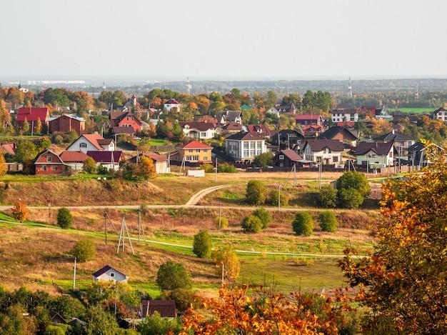 Słoneczna Jesień Wiejski Krajobraz Z Domami W Oddali. Rosja. Premium Zdjęcia
