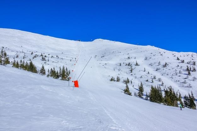 Słoneczna Pogoda W Ośrodku Narciarskim. Niebieskie Niebo. Długa I Prosta Trasa Z Armatkami śnieżnymi Premium Zdjęcia
