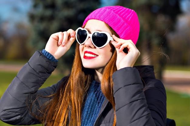 Słoneczny Wiosenny Portret Szczęśliwej Wesołej Uśmiechniętej Imbirowej Kobiety Pozującej W Parku, Ciesz Się Słonecznym Dniem, Jasnym Punkowym Kapeluszem Hipster, Serdecznymi Okularami Przeciwsłonecznymi, Czerwonymi Ustami, Ciepłą Parką, Pozytywnym Nastrojem. Darmowe Zdjęcia