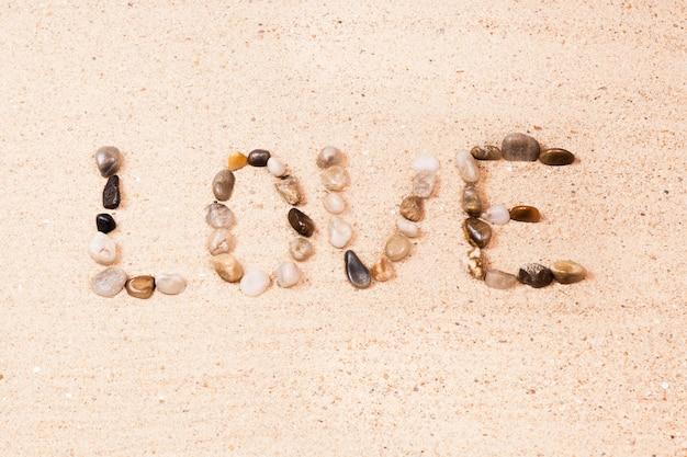 Słowo Miłość Pisać Z Otoczakami Na Piasku Plaża Premium Zdjęcia