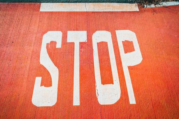 Słowo Stop Pomalowane Białymi Dużymi Literami Na Czerwonej Podłodze. Premium Zdjęcia