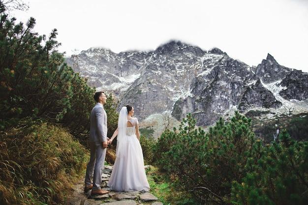 Ślubna para chodzi blisko jeziora w tatrzańskich górach w polska, morskie oko Premium Zdjęcia
