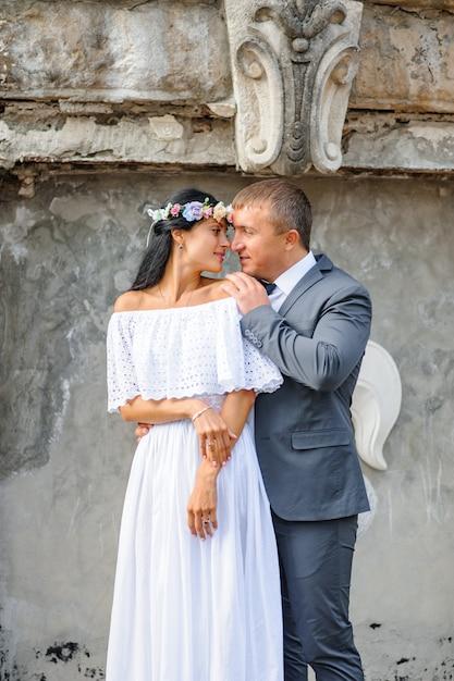 Ślubna Sesja Zdjęciowa Na Tle Starego Budynku. Państwo Młodzi Delikatnie Się Przytulają. Premium Zdjęcia