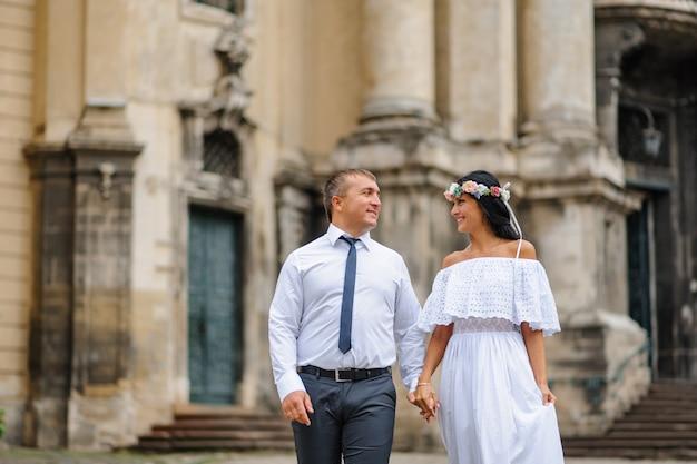 Ślubna Sesja Zdjęciowa Na Tle Starego Kościoła. Panna Młoda I Pan Młody Idą Razem. Mężczyzna Trzyma Rękę Kobiety. Fotografia ślubna W Stylu Rustykalnym Lub W Stylu Boho Premium Zdjęcia