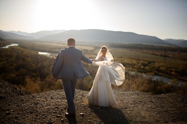 Ślubna Sesja Zdjęciowa Pary Młodej W Górach. Sesja Zdjęciowa O Zachodzie Słońca. Premium Zdjęcia
