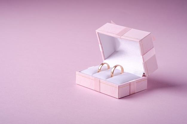 Ślubni Złociści Pierścionki W Różowym Prezenta Pudełku Na Miękkiej Części Różowym Tle, Kąta Widok, Kopii Przestrzeń Premium Zdjęcia