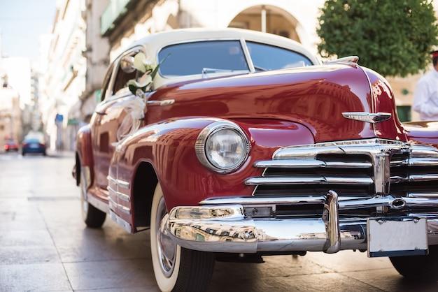 Ślubny bukiet na czerwonym rocznika ślubnym samochodzie. Premium Zdjęcia