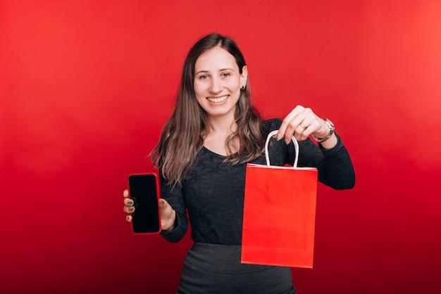 Słuchaj, Kupiłem To Online. Szczęśliwa Młoda Kobieta Uśmiecha Się Do Kamery Pokazującej Torbę Na Zakupy I Telefon Komórkowy Na Czerwonej Przestrzeni. Premium Zdjęcia