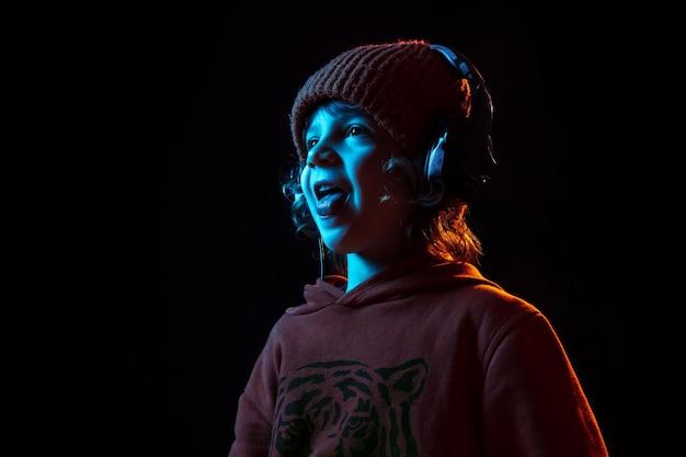 Słuchanie Muzyki I Tańca. Portret Kaukaski Chłopca Na Ciemnym Tle Studio W świetle Neonu. Piękny, Kręcony Model. Darmowe Zdjęcia