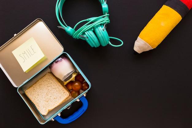 Słuchawki i piórnik w pobliżu lunchboxu Darmowe Zdjęcia