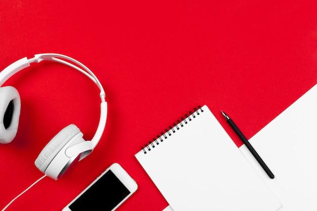 Słuchawki z przewodem na czerwonym i białym kolorze tła Premium Zdjęcia