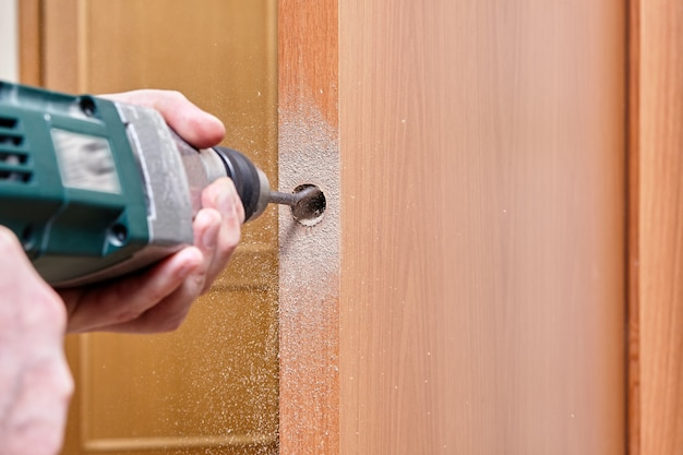 Ślusarz Używa Płaskiego Wiertła Do Drewna Podczas Wiercenia Otworu Na Zatrzask. Premium Zdjęcia
