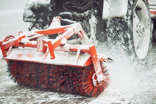 Służba miejska odśnieżająca, mały ciągnik z obracającą się szczotką czyści drogę w parku miejskim ze świeżego opadłego śniegu w zimowy dzień, pędzel - zbliżenie. Premium Zdjęcia