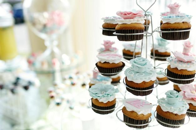 Smaczne babeczki z różowymi i niebieskimi szkliwami umieszczane są w uchwytach Darmowe Zdjęcia