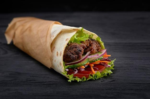 Smaczne Kebaby Donerowe Ze świeżymi Dodatkami Do Sałatek I Ogolonym Pieczonym Mięsem Podawane W Opakowaniach Tortilli Na Brązowym Papierze Jako Przekąska Na Wynos Premium Zdjęcia
