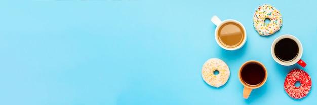 Smaczne Pączki I Kubki Z Gorącymi Napojami, Kawą, Cappuccino, Herbatą Na Niebieskiej Powierzchni. Koncepcja Słodyczy, Piekarni, Ciastek, Kawiarni, Spotkania, Przyjaciół, Przyjaznego Zespołu. Leżał Płasko, Widok Z Góry Premium Zdjęcia