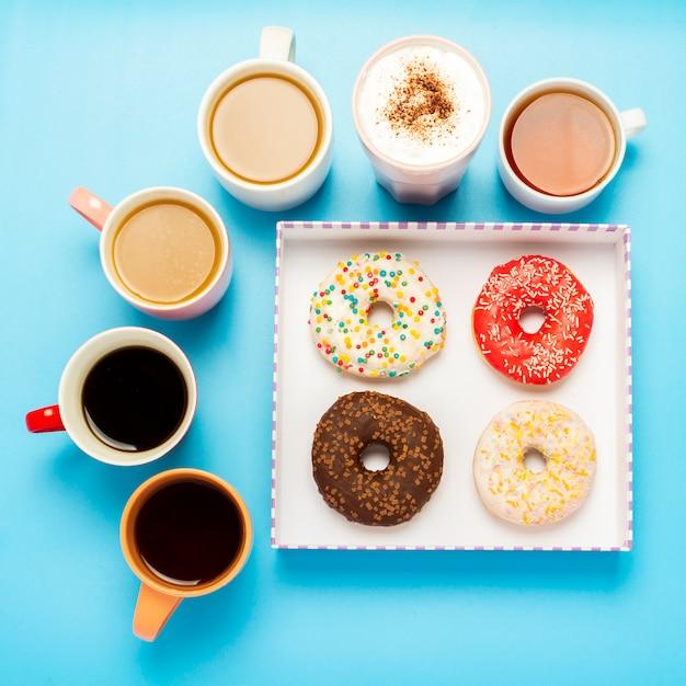 Smaczne Pączki I Kubki Z Gorącymi Napojami, Kawą, Cappuccino, Herbatą Na Niebieskiej Powierzchni. Premium Zdjęcia