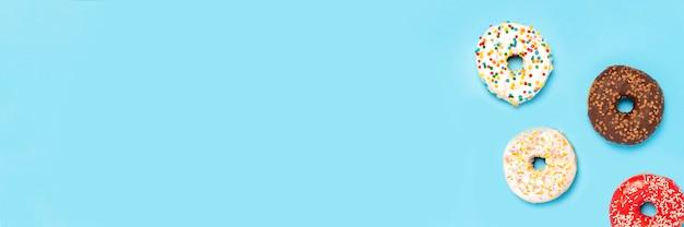 Smaczne Pączki Różnego Rodzaju Na Niebieskiej Powierzchni. Pojęcie Słodyczy, Piekarni, Ciastek. . Leżał Płasko, Widok Z Góry Premium Zdjęcia