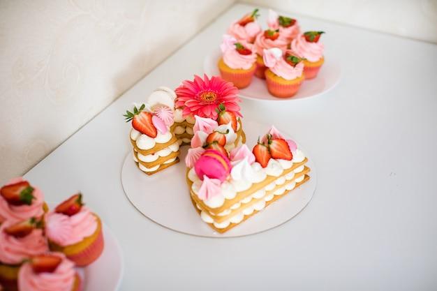 Smaczne, Piękne Różowe Ciasto Z Truskawkami, Piankami, Makaronikami I Ogromnym Kwiatkiem Na 2 Urodziny. Premium Zdjęcia