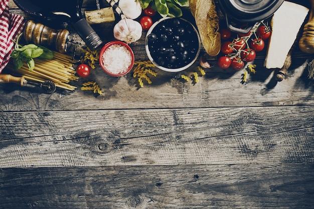 Smaczne świeże apetyczne włoskie składniki żywności na starym rustykalnym drewnianym tle. gotowy do gotowania. strona główna włoskiej kuchni zdrowej żywności koncepcji. tonowanie. Darmowe Zdjęcia