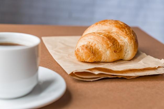 Smaczny Breackfast. Francuski Rogalik Podawany Na Papierze Rzemieślniczym I Filiżance Czarnej Kawy Lub Espresso Na Brązowym Tle. Transparent Premium Zdjęcia